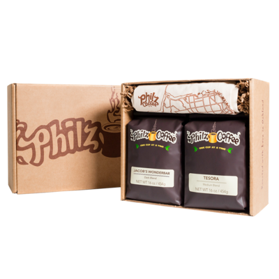 A Philz Box with the logo on it with 1 bag of Jacob's Wonderbar coffee, 1 bag of Tesora coffee, 1 Philz tote bag and crinkle paper in the box.
