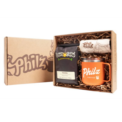A Philz Box with the logo on it with 1 bag of Tesora coffee, 1 Philz tote bag, 1 orange 12 oz mug, and crinkle paper in the box.