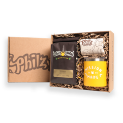 A Philz Box with the logo on it with 1 bag of Tesora coffee, 1 yellow camper mug, 1 Philz tote bag and crinkle paper in the box.
