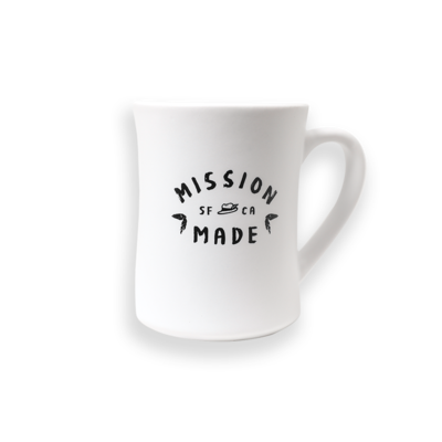 "White mug with ""Mission Made"" printed in black on the back."