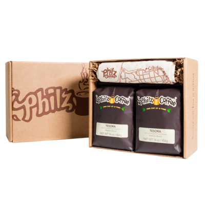 A Philz Box with the logo on it with 2 bags of Tesora coffee, 1 Philz tote bag, and crinkle paper in the box.